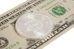 银色bitcoin硬币和一美元钞票 免版税库存图片