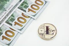 银色litecoin和100美元 免版税库存照片