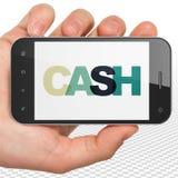 银行业务概念:拿着有现金的手智能手机在显示 图库摄影