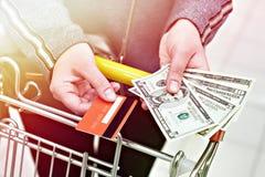 银行卡和美金在手中在商店 免版税库存照片