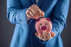 银行票据贪心放置的节省额 拿着桃红色贪心和投入的硬币的商人入存钱罐 免版税图库摄影