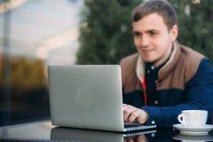 年轻银行雇员研究膝上型计算机在午餐时间 免版税图库摄影