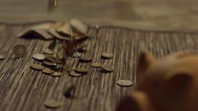 铸造从存钱罐倾吐的金钱 背景概念饮食金黄蛋的财务 股票视频