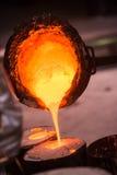 铸造厂工作者倾吐高热金属入塑象 免版税库存图片