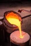 铸造厂工作者倾吐高热金属入塑象 免版税库存照片