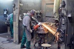 铸造厂研磨铸件的工作者与一台磨床-他 免版税库存照片