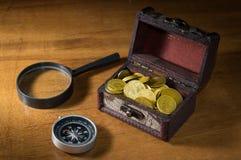 铸造在与指南针和放大镜的宝物箱 免版税库存图片