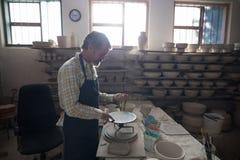 铸造在瓦器轮子的男性陶瓷工黏土 库存图片
