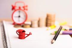 铸造堆和红色闹钟有色的铅笔的在笔记本 库存图片