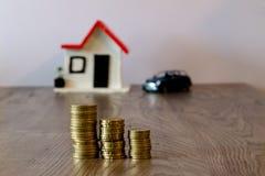 铸造堆在一张木桌顶部,与一辆被弄脏的房子和汽车在背景:房地产,房子抵押,储款概念 库存图片