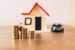 铸造堆在一张木桌顶部,与一辆被弄脏的房子和汽车在背景:房地产,房子抵押,储款概念 图库摄影