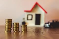 铸造堆在一张木桌顶部,与一辆被弄脏的房子和汽车在背景:房地产,房子抵押,储款概念 免版税库存照片