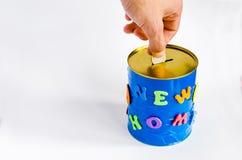 铸造插入物入有新的家庭题字的一个手工制造钱箱在白色背景 顶视图 免版税库存照片