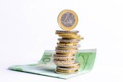 铸造欧元 背景欧洲货币白色 在一百张钞票 许多在另一个位置的硬币 免版税库存照片