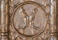 铸造的银色表面上的两条鱼 库存图片