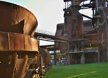 铸钢的老生锈的杯子在一个绿色领域在一家被放弃的钢铁制品工厂 库存照片