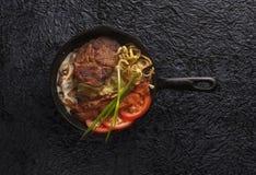 铸铁平底锅用肉,大角度看法 黑色背景 免版税库存照片