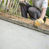铺平新近地被放置的混凝土的工作者 免版税库存图片