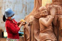铺沙一个佛教木雕象的妇女 免版税库存照片