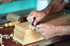 铺沙一块木头的家具工的手 免版税库存照片