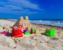 铺沙与在海滩修造的孩子玩具的城堡 免版税库存图片