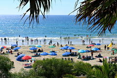 铺沙与许多人民和伞的小河海滩 库存照片