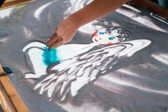 铺沙动画,画的沙子特写镜头,画在沙子的女孩一个天使 免版税库存照片