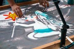 铺沙动画,画的沙子特写镜头,画在沙子的女孩一个天使 免版税图库摄影