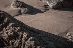 铺沙在海滩的一个岩石 免版税库存图片