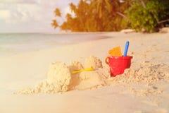 铺沙在热带海滩的城堡并且哄骗玩具 图库摄影
