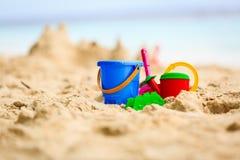 铺沙在热带海滩的城堡并且哄骗玩具 免版税库存图片