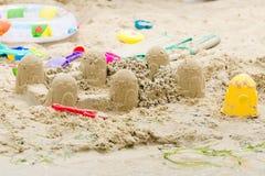 铺沙城堡圈子和玩具在河岸 库存照片
