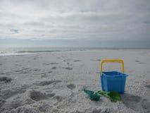 铺沙城堡大厦工具和桶在海滩 免版税图库摄影