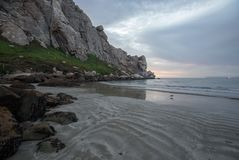 铺沙样式在日落在加利福尼亚中央海岸的Morro岩石潮汐入口在莫罗贝加利福尼亚美国 免版税库存照片