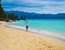 铺沙海滩、绿松石用密林盖的水、小山和重的风雨如磐的天空 免版税库存照片