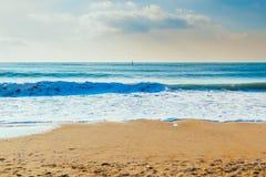 铺沙海滩和海浪在蓝天下 库存照片