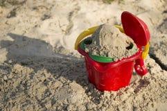 铺沙玩具、一个红色桶和一个瓢在沙子, 库存图片