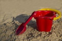铺沙玩具、一个红色桶和一个瓢在沙子, 库存照片