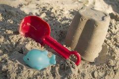 铺沙玩具、一个红色桶和一个瓢在沙子, 免版税库存照片