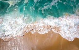 铺沙空中的海滩,美丽的沙滩空中射击的顶视图与滚动入岸的蓝色波浪的 免版税库存照片