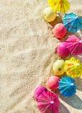 铺沙纹理(背景)用与伞的五颜六色的复活节彩蛋在海滩 库存图片