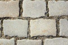 铺磁砖与铺路石砖道路的片段作为抽象背景 免版税库存照片