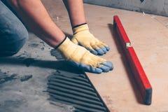 铺磁砖工在地板上把瓦片放 库存照片