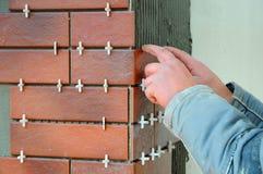 铺磁砖工安装装饰瓦片的建筑工人在大厦的门面 被绝缘的和涂灰泥的门面 未完成的co 库存照片