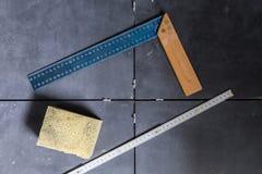 铺磁砖概念工具,角度,统治者,在瓦片顶视图的海绵 免版税库存照片