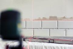 铺磁砖瓦片的过程在使用建筑la的厨房里 库存照片