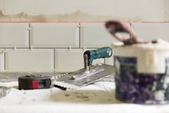 铺磁砖瓦片的过程在有必要的盖瓦的厨房里 免版税库存照片