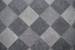 铺磁砖的地板在方形的黑和灰色背景中 免版税库存图片