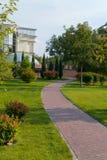 铺磁砖的轨道那导致有玻璃圆顶的房子在一个美丽的公园 免版税库存照片