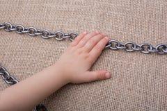 链子手中由的金属制成在帆布 免版税库存图片